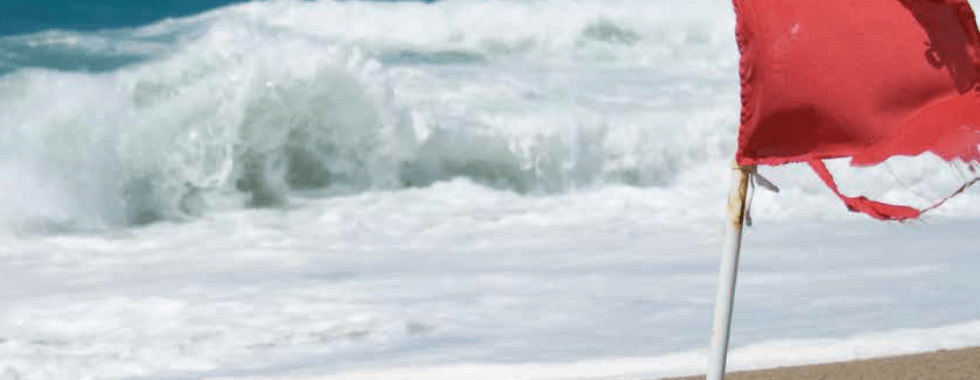 image of a red warning flag at the beach